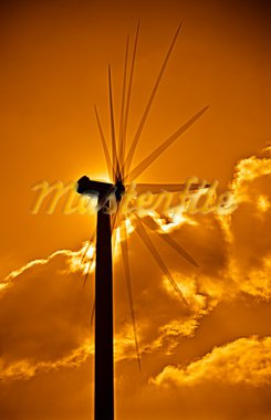 Wind turbine in the back light of the sun with yellow sky and clouds. Stock Photo - Royalty-Free, Artist: homydesign                    , Code: 400-05386970
