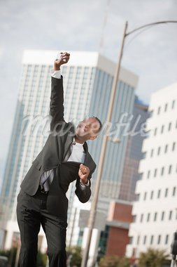 Excited Black businessman with phone in hand leaps in their air Stock Photo - Royalty-Free, Artist: creatista                     , Code: 400-05388077