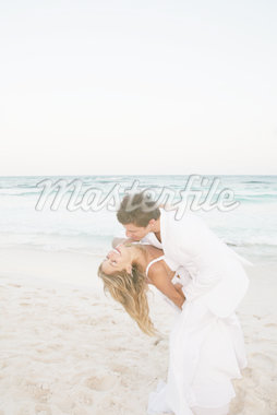 Man dipping woman on sandy beach Stock Photo - Premium Royalty-Freenull, Code: 6106-05439481