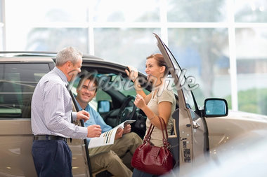 Salesman showing off car in showroom Stock Photo - Premium Royalty-Freenull, Code: 649-05521312