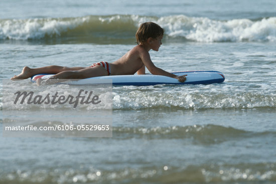 Boy (8-9) floating on airbed in sea, side view Stock Photo - Premium Royalty-Freenull, Code: 6106-05529653