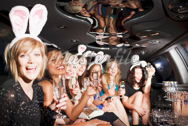 Women in bunny ears toasting in back of limo Stock Photo - Premium Royalty-Freenull, Code: 635-05550066