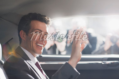 Politician waving from backseat of car Stock Photo - Premium Royalty-Freenull, Code: 635-05550089