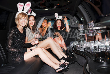 Women in bunny ears drinking champagne in limo Stock Photo - Premium Royalty-Freenull, Code: 635-05550132