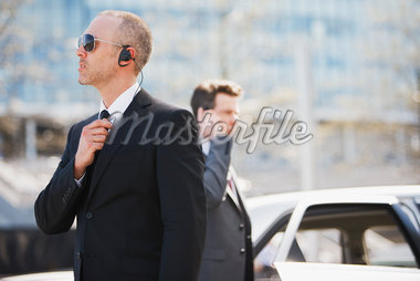Bodyguard talking into earpiece Stock Photo - Premium Royalty-Freenull, Code: 635-05550142