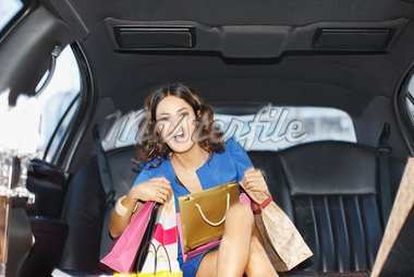 Woman with shopping bags in backseat of limo Stock Photo - Premium Royalty-Freenull, Code: 635-05550176