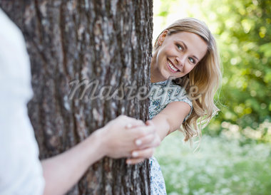 Couple holding hands around tree Stock Photo - Premium Royalty-Freenull, Code: 635-05550226