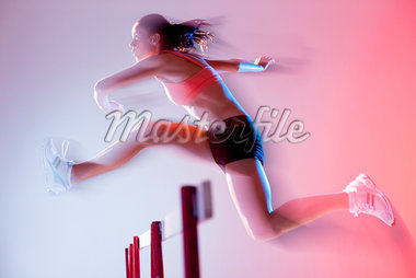 Blurred view of runner jumping hurdles Stock Photo - Premium Royalty-Freenull, Code: 635-05550494