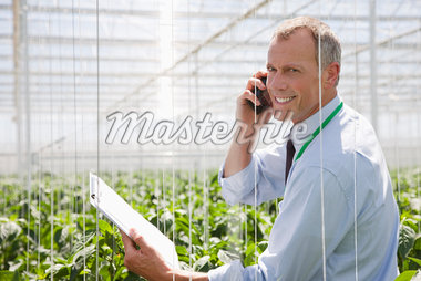 Businessman talking on cell phone in greenhouse Stock Photo - Premium Royalty-Freenull, Code: 635-05550712