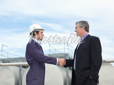 Worker and businessman shaking hands outdoors Stock Photo - Premium Royalty-Freenull, Code: 635-05550926