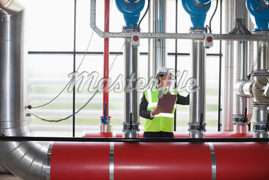 Businessman checking pipes in factory Stock Photo - Premium Royalty-Freenull, Code: 635-05550938