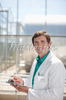 Scientist writing on clipboard outdoors Stock Photo - Premium Royalty-Freenull, Code: 635-05551016