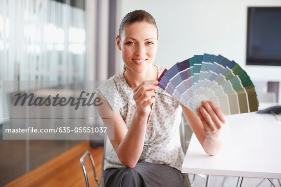 Businesswoman with paint swatches in office Stock Photo - Premium Royalty-Freenull, Code: 635-05551037