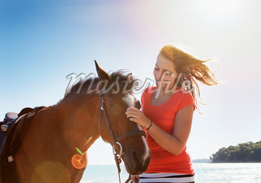 Girl petting horse outdoors Stock Photo - Premium Royalty-Freenull, Code: 635-05551103