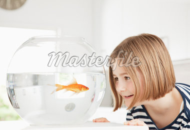 Girl examining goldfish in fishbowl Stock Photo - Premium Royalty-Freenull, Code: 635-05551104