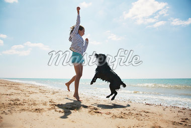 Girl playing with dog on beach Stock Photo - Premium Royalty-Freenull, Code: 635-05551128