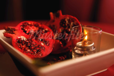 Pomegranates and candle centerpiece. Stock Photo - Premium Royalty-Freenull, Code: 618-05551341