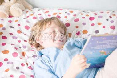 Young boy reading a book on his bed Stock Photo - Premium Royalty-Freenull, Code: 614-05650627