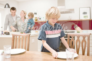 Son helping to lay table with parents and brother visible behind in kitchen Stock Photo - Premium Royalty-Freenull, Code: 614-05650637