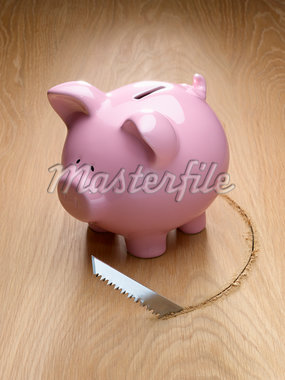 Saw cutting a hole around a piggy bank Stock Photo - Premium Royalty-Freenull, Code: 635-05651401