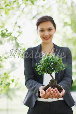 Businesswoman standing outdoors holding plant Stock Photo - Premium Royalty-Freenull, Code: 635-05651497