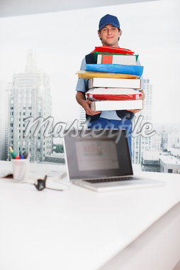 Deliveryman carrying boxes in office Stock Photo - Premium Royalty-Freenull, Code: 635-05651555
