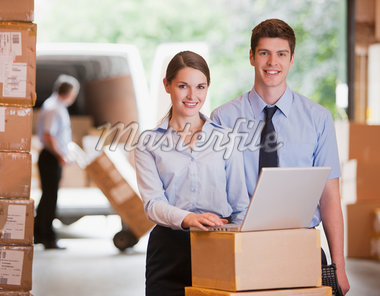 Business people working with laptop in warehouse Stock Photo - Premium Royalty-Freenull, Code: 635-05651581
