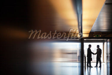 Businessman shaking hands together in corridor Stock Photo - Premium Royalty-Freenull, Code: 635-05651643