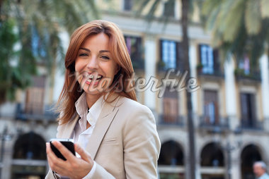 Smiling businesswoman text messaging on cell phone Stock Photo - Premium Royalty-Freenull, Code: 635-05651645