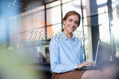 Businesswoman using laptop in lobby Stock Photo - Premium Royalty-Freenull, Code: 635-05651687