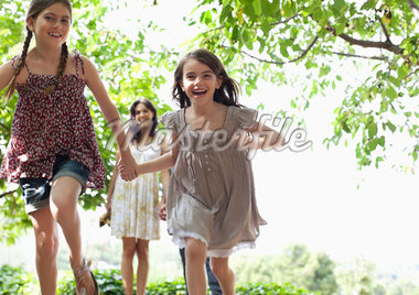 Girls holding hands and running outdoors Stock Photo - Premium Royalty-Freenull, Code: 635-05651765