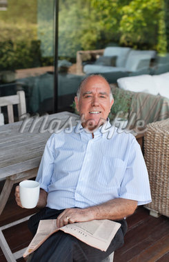 Man sitting on patio drinking coffee and reading newspaper Stock Photo - Premium Royalty-Freenull, Code: 635-05651769