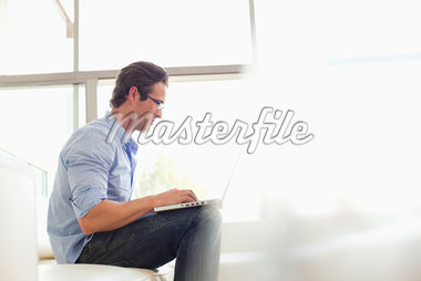Man sitting on sofa using laptop Stock Photo - Premium Royalty-Freenull, Code: 635-05651801