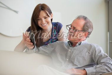 Father showing cell phone to daughter Stock Photo - Premium Royalty-Freenull, Code: 635-05651879