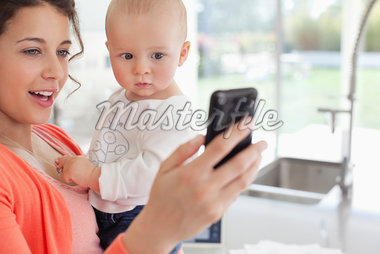 Mother holding baby and using cell phone Stock Photo - Premium Royalty-Freenull, Code: 635-05651880