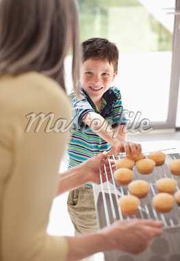 Grandmother offering cupcakes to grandson Stock Photo - Premium Royalty-Freenull, Code: 635-05652226