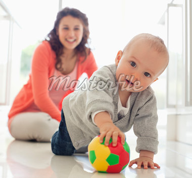 Mother watching baby playing with ball Stock Photo - Premium Royalty-Freenull, Code: 635-05652240