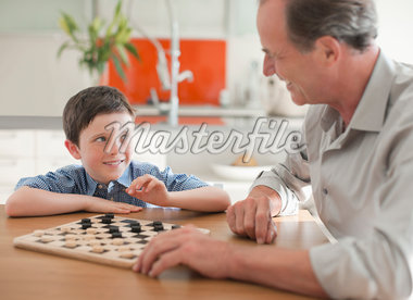 Grandfather and grandson playing checkers together Stock Photo - Premium Royalty-Freenull, Code: 635-05652263
