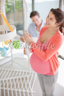 Expectant mother looking at crib mobile Stock Photo - Premium Royalty-Freenull, Code: 635-05652283