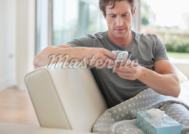 Sick man checking medicine package Stock Photo - Premium Royalty-Freenull, Code: 635-05652413