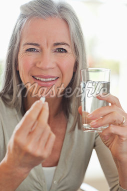 Woman holding glass of water and taking pill Stock Photo - Premium Royalty-Freenull, Code: 635-05652416