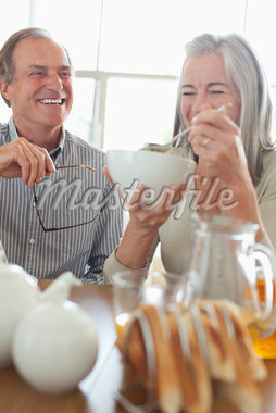 Senior couple laughing at breakfast Stock Photo - Premium Royalty-Freenull, Code: 635-05655678