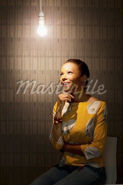 Pensive businesswoman sitting under illuminated light bulb Stock Photo - Premium Royalty-Freenull, Code: 635-05655932