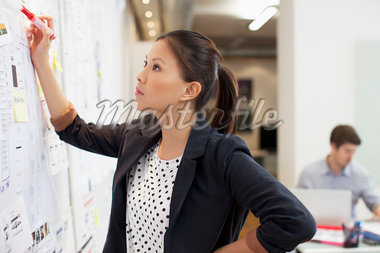 Businesswoman looking at information on whiteboard in office Stock Photo - Premium Royalty-Freenull, Code: 635-05655946
