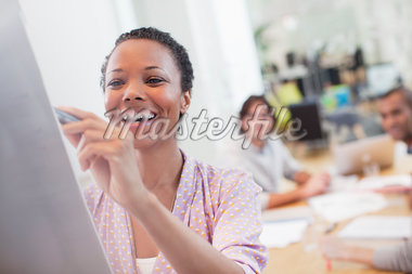 Smiling woman writing on whiteboard in conference room Stock Photo - Premium Royalty-Freenull, Code: 635-05655968