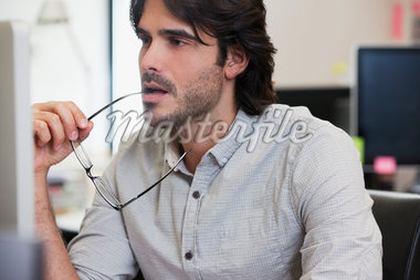 Pensive businessman working on computer in office Stock Photo - Premium Royalty-Freenull, Code: 635-05655972