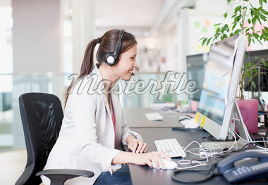 Businesswoman with headset using computer in office Stock Photo - Premium Royalty-Freenull, Code: 635-05656051