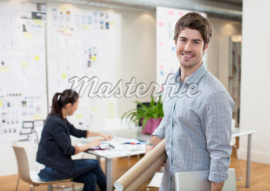 Portrait of smiling architect holding blueprint tubes in office Stock Photo - Premium Royalty-Freenull, Code: 635-05656062