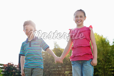 Portrait of smiling boy and girl holding hands Stock Photo - Premium Royalty-Freenull, Code: 635-05656124
