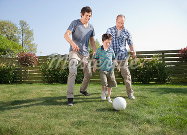 Multi-generation family playing soccer in backyard Stock Photo - Premium Royalty-Freenull, Code: 635-05656128